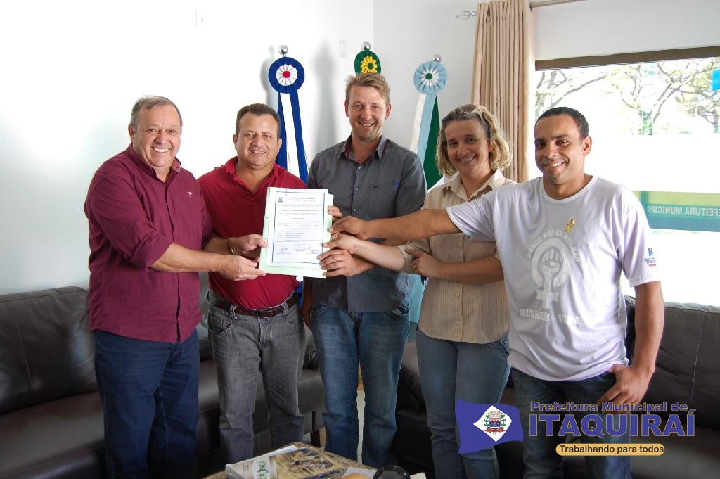 Prefeito ricardo fávaro e o diretor de cadastro altair muller entregam título definitivo de imóvel para a diretoria do sindicato dos servidores públicos municipais de itaquiraí